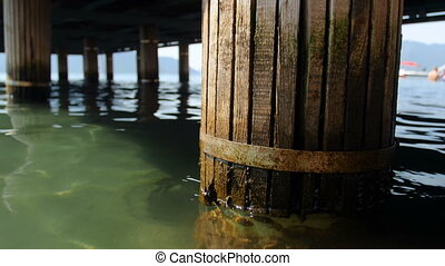 4k closeup footage of old wooden column supporting pier in...