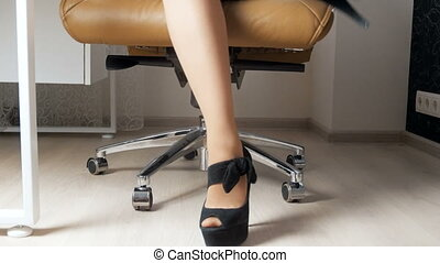 4k closeup footage of sexy businesswoman with long legs and high heels sitting on office chair