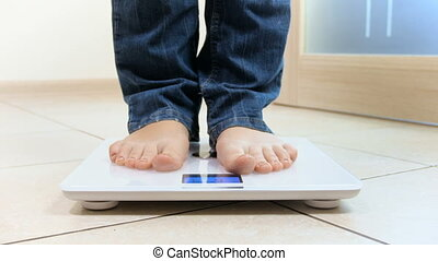 4k closeup footageof young woman standing on electronic scales