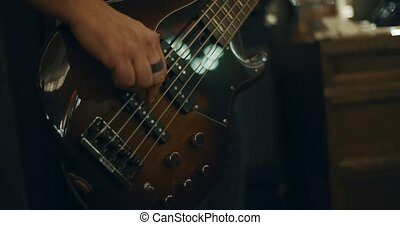 4K Closeup of fingers playing an electric guitar in a home...
