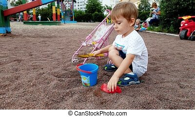 4k closeup video of adorable toddler boy digging sand with...