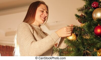 4k closeup video of happy smiling young woman decorating Christmas tree with baubles in living room
