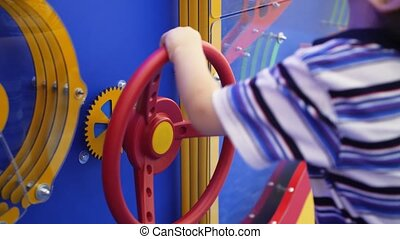 4k closeup video of little boy turning big colorful valve on...
