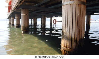 4k closeup video of old wooden columns holding pier on sea...
