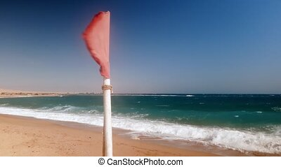4k closeup video of red flag fluttering on the beach at...