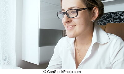 4k closeup video of young smiling businesswoman wearing eyeglasses working at office and looking at computer screen