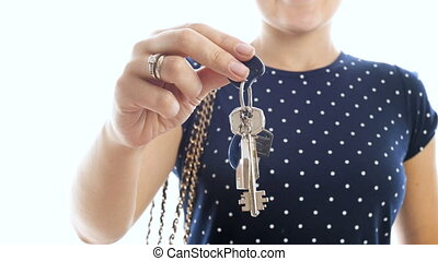 4k closeup video of young smiling woman holding home keys against white background