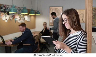 4k. closeup young attractive brunette businesswoman uses a touchscreen tablet in the modern startup office.