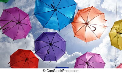 4K Colorful umbrella hanging against cloudy blue sky