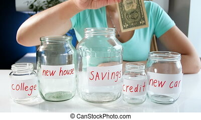 4k conceptual footage of young woman choosing where to invest money. She is putting one dollar in moneybox labeled New house