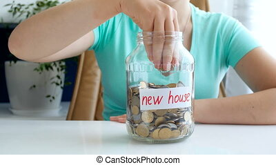 4k conceptual video of young woman collecting and saving money for new house. Little toy house appeairng on table