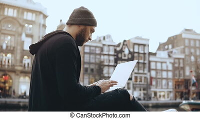 4K Creative man sitting with laptop in the street. Working...