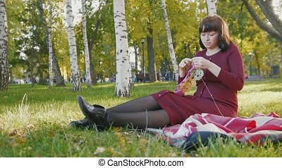 4K Cute happy pregnant woman in red dress sitting on blanket and make knitting in the autumn park at sunset, slide shot