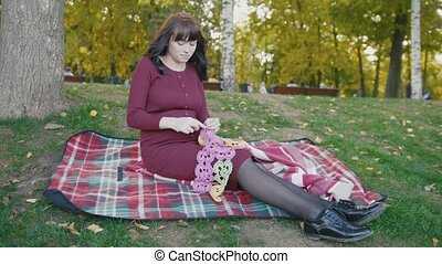 4K Cute happy pregnant woman in red dress sitting on blanket in the autumn park at sunset, slide shot