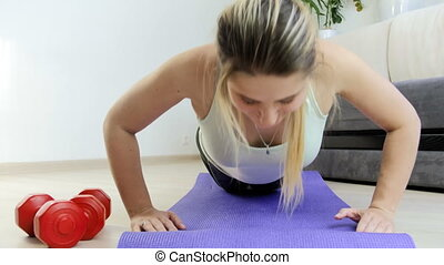 4k dolly footage of young woman with long hair doing push-ups on fitness mat at home