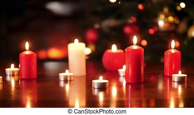 4k dolly video of lots of burning red and white candles on wooden table against Christmas tree