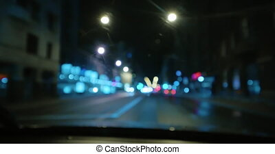4K - Driving at night on town streets. Front car window with blurred city traffic