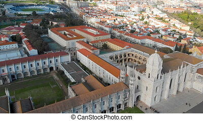 4k drone aerial view of Empire Square and the Jeronimos Monastery in Lisbon. Portugal with cityscape in background.