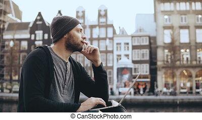 4K European adult man sitting with laptop outside. Popular...
