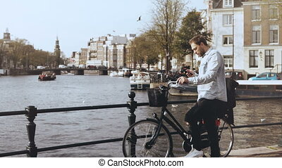 4K European man with bicycle on a river bridge. Casual...