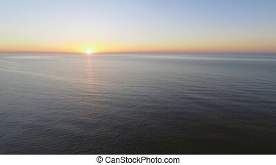 4K Flying over the sea towards rising sun - Aerial footage...