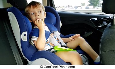 4k footage of 3 years toddler boy sitting in child car...