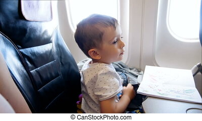 4k footage of adorable 2 years old toddler boy looking in airplane illuminator during flight