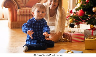 4k footage of adorable smiling toddler boy sitting with mother under Christmas tree at morning