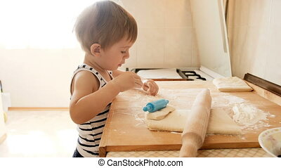 4k footage of adorable toddler boy playing with dough while making pie on kitchen