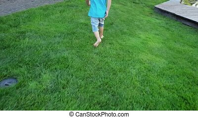 4k footage of barefoot toddler boy running on fresh green...