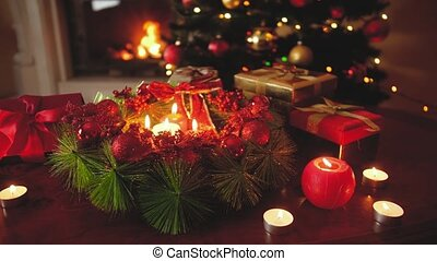 4k footage of beautiful decorated advent wreath with burning candles against glowing Christmas tree. Perfect background or backdrop for Christmas or New Year