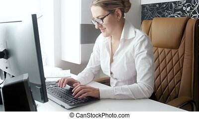 4k footage of beautiful smiling businesswoman sitting behind modern white desk in office and working on computer