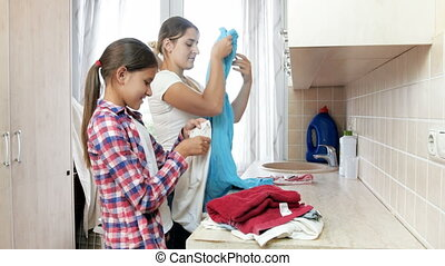 4k footage of beautiful smiling girl helping her mother doing housework in laundry