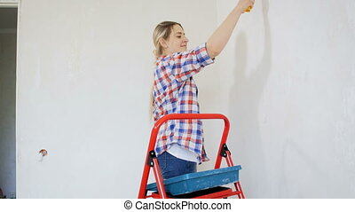 4k footage of beautiful smiling woman painting wall with roller