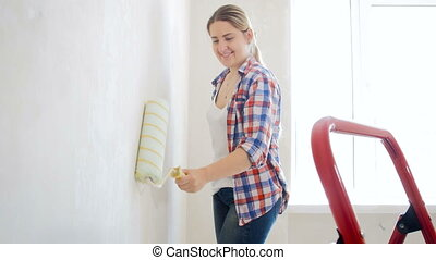 4k footage of beautiful smiling woman painting wall with roller at new home
