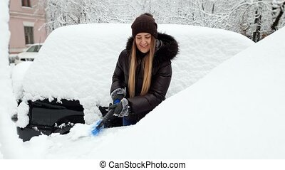4k footage of beautiful smiling young woman removing snow...