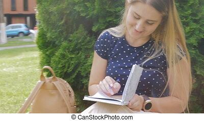 4k footage of beautiful young girl sitting on grass at park at sunny day and writing in diary