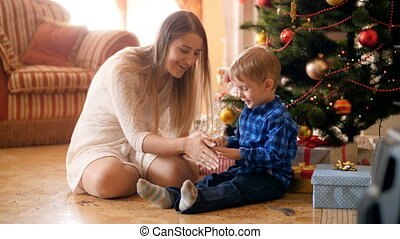 4k footage of beautiful young mother playing with her little boy under Christmas tree and throwing confetti