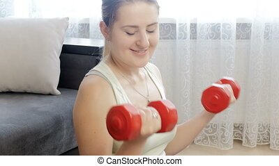 4k footage of beautiful young woman exercising at home with red dumbbells