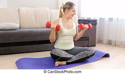 4k footage of beautiful young woman exercising with dumbbells on fitness mat at home