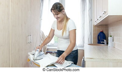 4k footage of beautiful young woman ironing clothes on board...