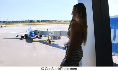 4k footage of beautiful young woman standing at big window...