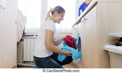 4k footage of beautiful young woman taking clean clothes out...