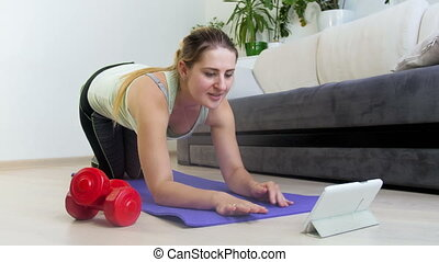 4k footage of beautiful young woman watching motivational video of digital tablet while exercising on fitness mat