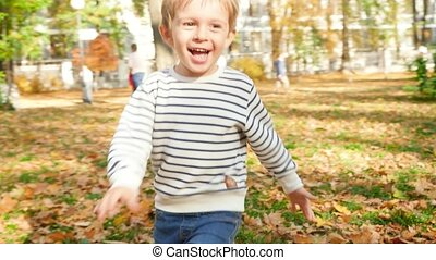 4k video of cheerful smiling and laughing little boy running and chasing camera in autumn park