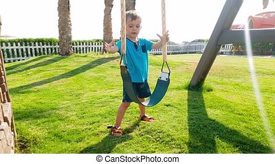 4k footage of cheerful toddler boy playing on the playground with swing at sunny summer day