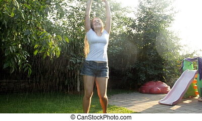 4k footage of cheerful young woman enjoying rain on hot summer day at backyard