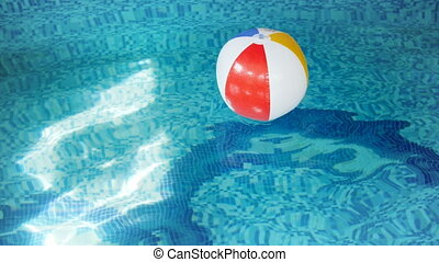 4k footage of colorful striped beach ball swimming in pool....