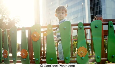 4k footage of cute smiling toddler boy standing on wooden bridge at playground at sunset