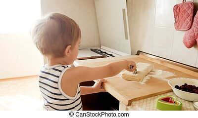 4k footage of cute toddler boy cutting dough on wooden board with round cutter knife